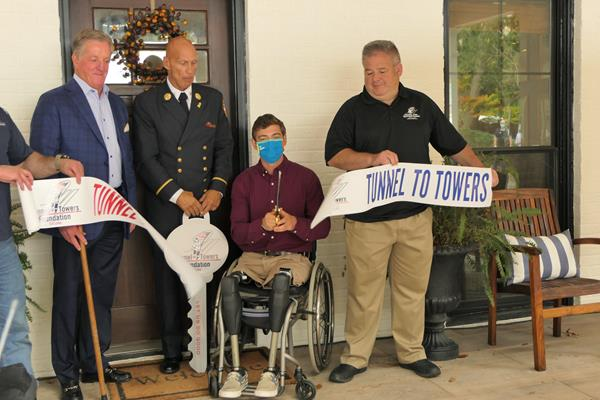 U.S. Army Captain Dan Berschinski cuts a ceremonial ribbon outside of his Atlanta home.