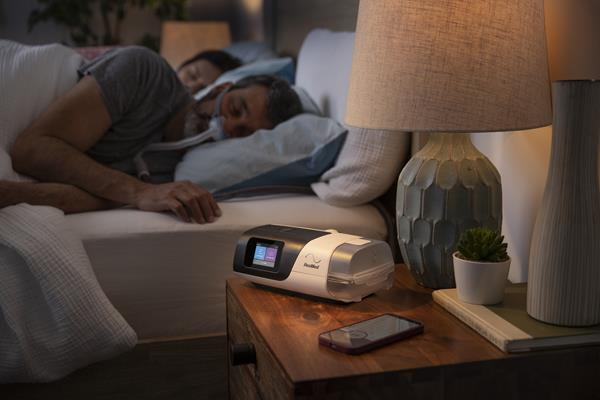 Man Sleeping using Nasal Pillow with AirSense 11 and Phone on Nightstand