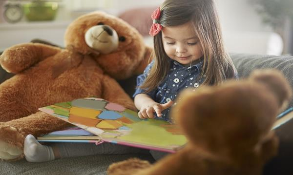 Child reading to her toy teddy bears