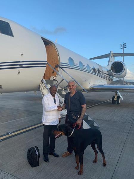 Alki David, CEO of Swissx, with former St. Kitts-Nevis Prime Minister Denzil Douglas (left), who is on the board of the Swissx Bank of Cannabis. Pictured with the Swissx Express jet and Vader, David's Doberman who is the subject of a Swissx Genetics breakthrough cloning project.