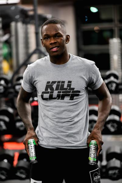 UFC Champion Israel Adesanya wears a Kill Cliff shirt and holds Kill Cliff drink cans standing in a gym
