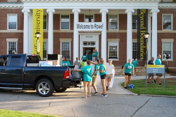 Teams of current students and employees greet new students and help move them into their new home.