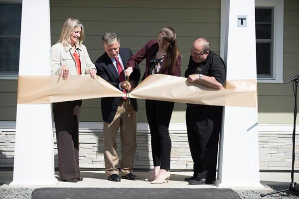 Participating in Husson University's ribbon cutting ceremony for their new townhouses were (from left to right), Pamela Kropp-Anderson, Husson University's dean of student life, Robert J. Ronan, '79, chair of the University Board of Trustees, Madeline Sanborn '18, a Husson student trustee pursuing a Bachelor of Science degree in health sciences, and Dr. Robert A. Clark, Husson University president.