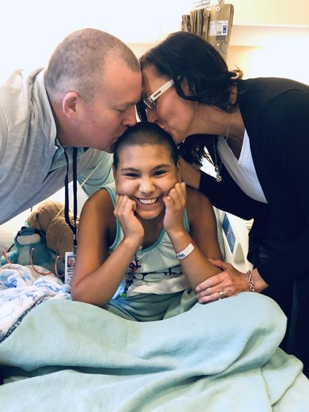 Emi receives kisses from her adoptive parents, Jason and Katie Ballard, at the NIH Clinical Center as she gets ready to receive a lifesaving hematopoietic stem cell transplant, the only way to cure her fatal immune deficiency, using cells donated by her birth mom.