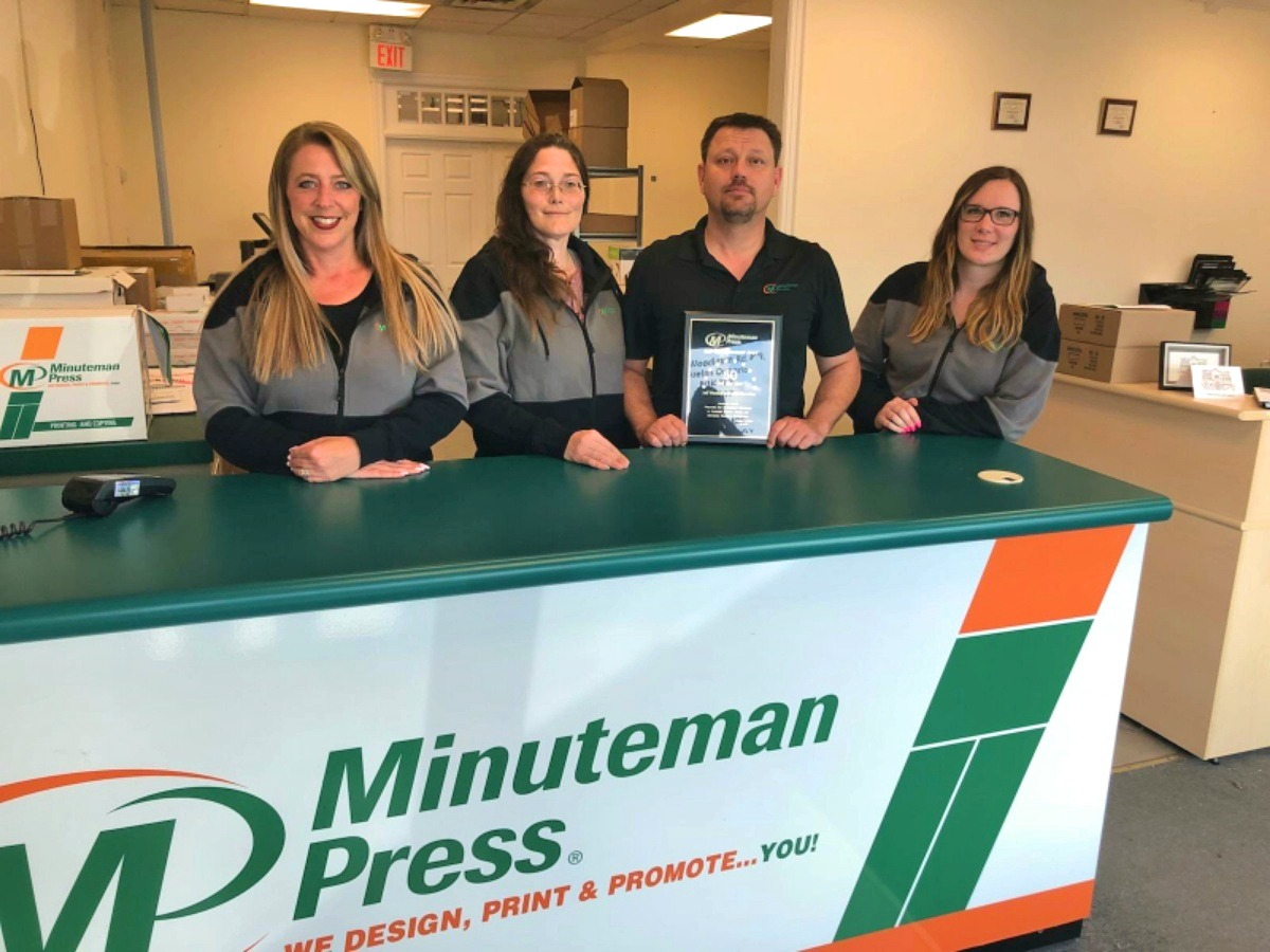 Karen McArthur and Jeff Wereley (middle) own the Minuteman Press design, marketing, and printing franchise in Guelph, Ontario, Canada.