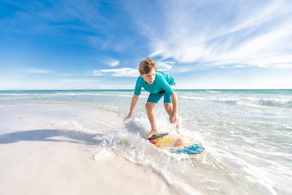 Skimboarding along the white sand beaches of Destin, Florida is one of the many ways beach activities that allow families to enjoy the outdoors while social distancing.