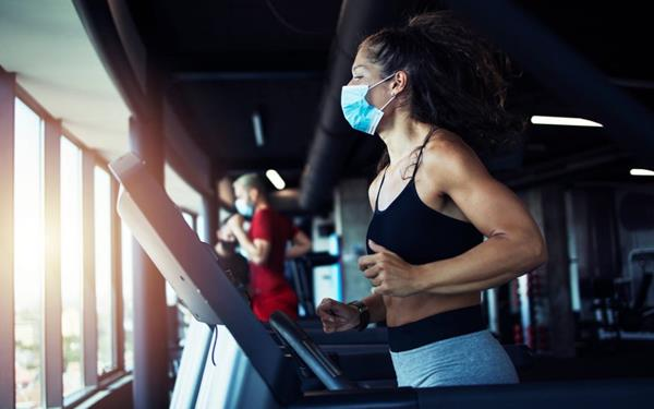 Woman working out at a clean and safe gym in Colorado, wearing a mask on a treadmill.