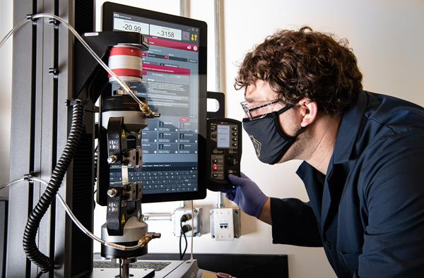 NREL researcher Nic Rorrer tests a sample of a new plastic formulation for its tensile properties. As part of Gregg Beckham's plastics research group, Rorrer is working on the redesign of nylon (aka polyamide) polymers so they can be chemically recycled with more efficient and less energy-intensive processes. Photo by Dennis Schroeder, NREL