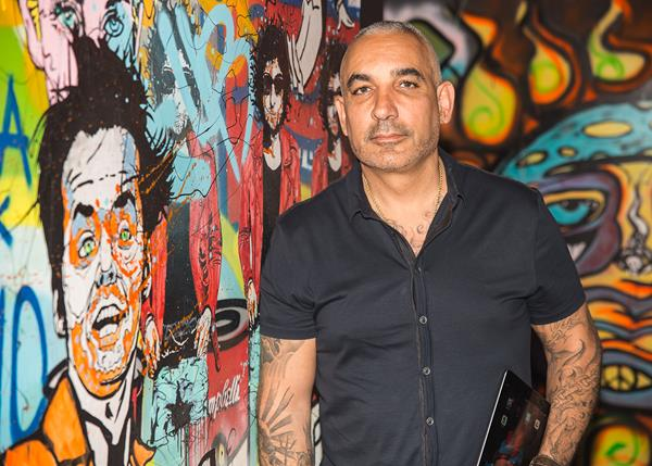 FilmOn TV CEO Alki David at his Hollywood office with a mural of Jack Nicholson and Bob Dylan by graffiti artist Alec Monopoly. Watch 1000s of movies and 600 channels at FilmOn.com