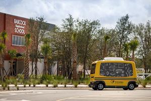 Yellow transdev autonomous shuttle parked outside Babcock Neighborhood School