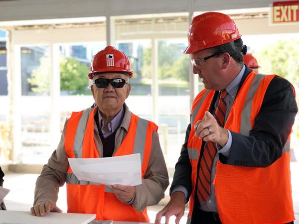 Kwang G. Tan, left, touring the construction site of the National Veterans Resource Center at the Daniel and Gayle D'Aniello Building.