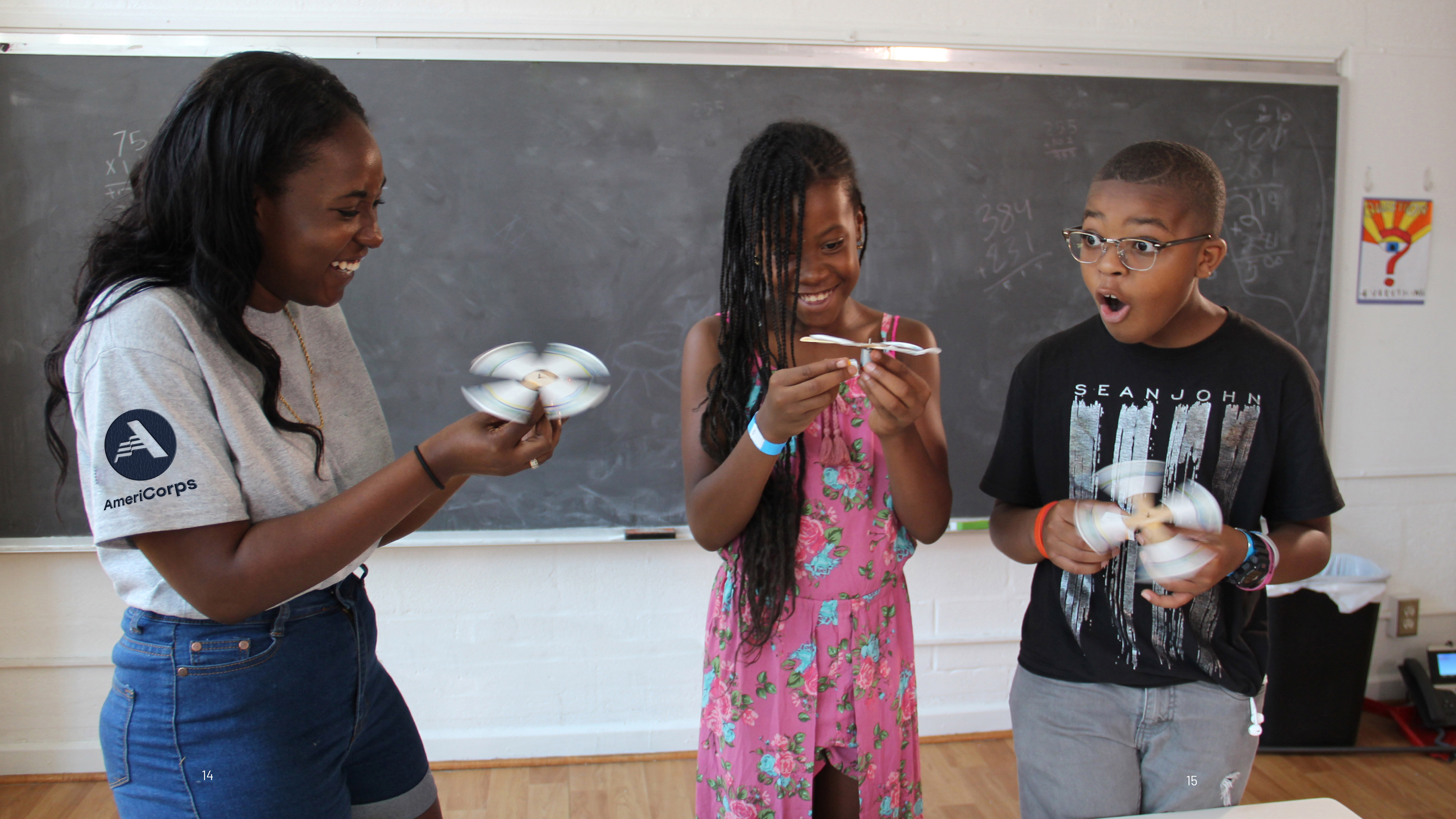 An AmeriCorps member demonstrates a STEM project in a classroom to two surprised students.