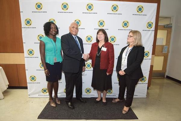 Ronald Moss, the Regional Administrator for Region II of the HRSA, and Julia Tsien shake hands.