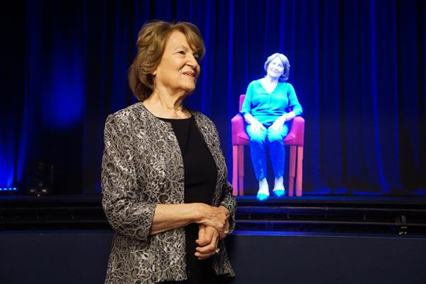 Fritzie in front of her hologram in Illinois Holocaust Museum's Survivor Stories Experience. (photo credit: Ron Gould)