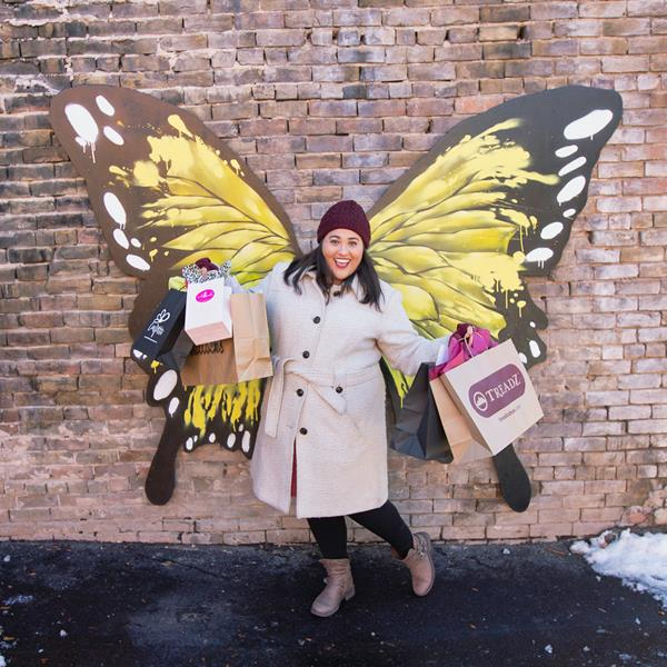 Woman posing in front of set of Glenwood Wings while enjoying historic downtown Glenwood Springs.