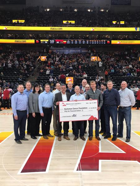 Mountain America senior leadership team presents a $56,000 check to David Huntsman, who represented Huntsman Cancer Foundation, at the Utah Jazz game on April 9, 2019.