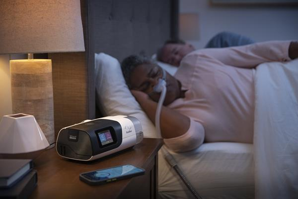 Woman Sleeping with Nasal Pillow with Device and Phone on Nightstand