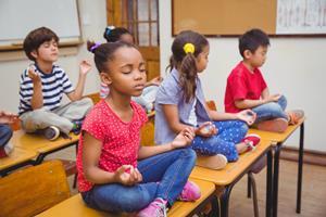 1_int_Diverse_Children_Meditating_On_Desks_Classroom.jpg