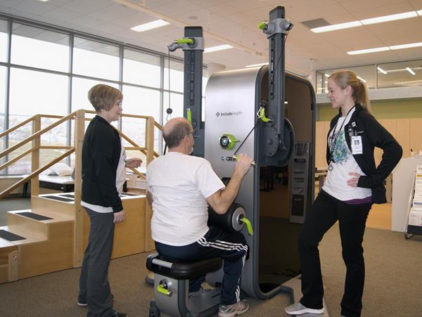 Phil Echert, a patient in the Muscle2Mind pilot program at HealthPartners, exercises with an IncludeHealth and the help of both his exercise physiologist Christa Lence and his caregiver Heather Echert.