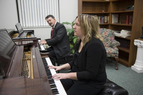 Dr. Chuck Clevenger plays a piece of music to help teach Macy McClain play the piano. Photo by Scott Huck