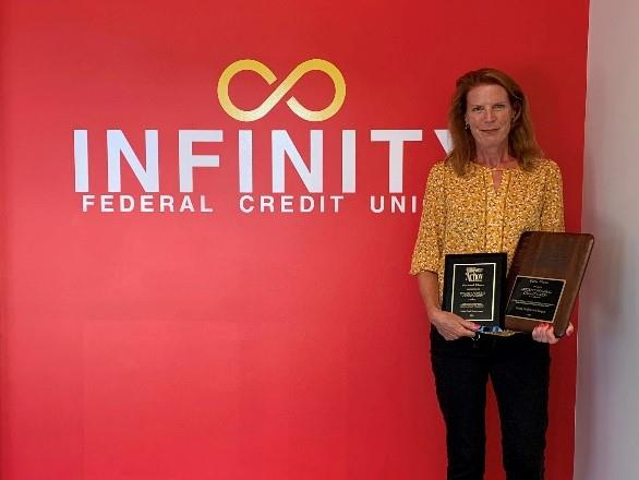 Elizabeth Hayes, Infinity Federal Credit Union (FCU) President and CEO, shown with the second-place Louise Herring Philosophy-in-Action Member Service Award and the first-place Dora Maxwell Social Responsibility Community Service Award.