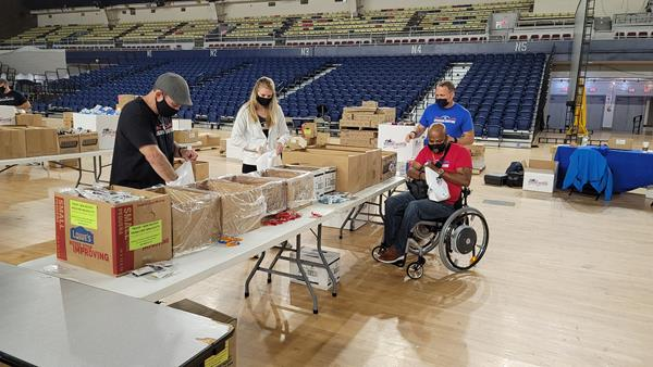 Schmiegel and Gillums assembling Operation Gratitude care packages for veterans on Veterans Day at the DC National Guard Armory.