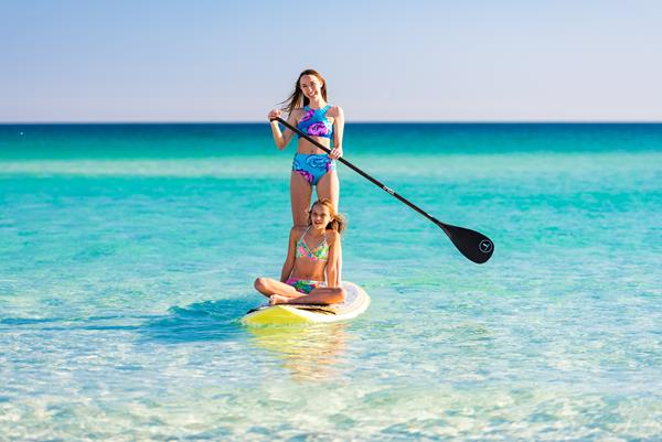 Outdoor adventure seekers enjoy stand-up paddle boarding along the emerald green waters around Destin, Florida searching for marine life including fish, sea turtles, and dolphins during their Labor Day vacation.