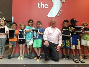 TCB President/CEO Phil Ryan with Parkway YMCA kids and the donated iPads