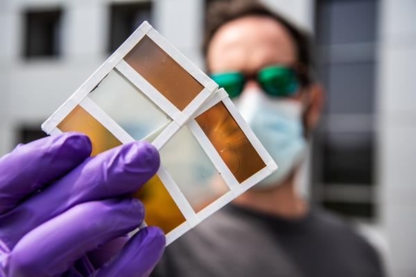 NREL researcher Lance Wheeler holds a perovskite window prototype that can switch between a variety of colors. Photo by Dennis Schroeder, NREL