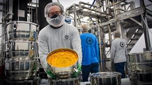 A vessel of crude oil weighing approximately 5 kg / 11 lb is held by a CLC extraction team member, showing the distinct golden hue of wax which will be removed in the distillation process, resulting in a finished oil product with a viscosity and colour similar to honey.