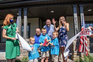 SFC Travis Vendela and his family cut the ribbon outside of his new mortgage-free smart home in Huntsville, Utah