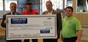 (Left to Right) Scott Swingle and Tom Peet of Southern Delaware Therapeutic Riding accept a check for $30,000 from Bruce O'Connor and Joseph Cuccinello representing Tidewater Utilities, Inc.  The check reflects the proceeds of Tidewater's  Annual  Charity Golf Outing.  Tidewater has raised more than $180,000 for various non-profit organizations through its charity outing over the last 12 years.
