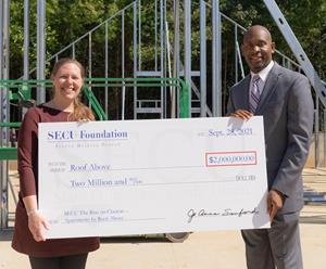 Liz Clasen-Kelly, Roof Above CEO (left), receives ceremonial check from Tyrone Tyler, SECU Regional Senior Vice President.