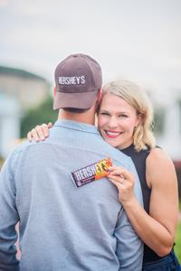 Jenny Ries holding the new HERSHEY'S Milk Chocolate Bar with REESE'S PIECES candy.