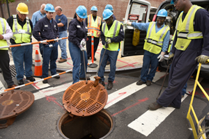 Con Edison workers test a latched manhole cover