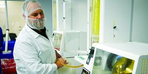 A cannabis processing technician outfitted in a lab jacket, hairnet and facemask, monitors an extraction machine