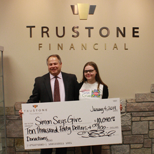 Tim Bosiacki, Chief Executive Officer at TruStone Financial, presents the donation check to Ainsley Cox, Youth Leader of the Kid Advisory Board at Simon Says Give